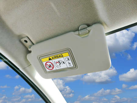 Car sun visor and warning signs of airbag system in car with sky and clouds as a backdrop.