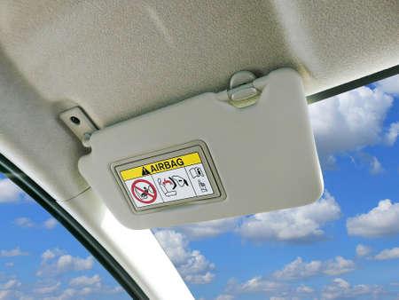 Pare-soleil de voiture et panneaux d'avertissement du système d'airbag dans la voiture avec le ciel et les nuages en toile de fond. Banque d'images