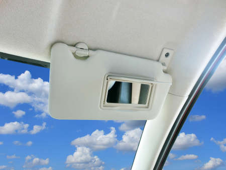 Car sun visor and mirror in car with sky and clouds as a backdrop.