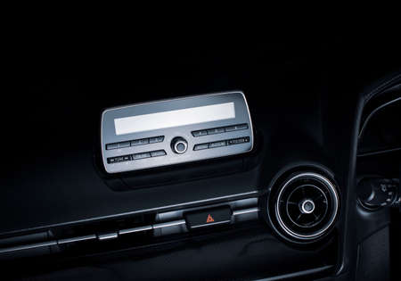 Audio multimedia player and radio on car console panel and emergency light button in a luxury car. Stock Photo