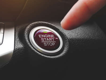Car driver press to the engine start stop button for engine ignition in a luxury car