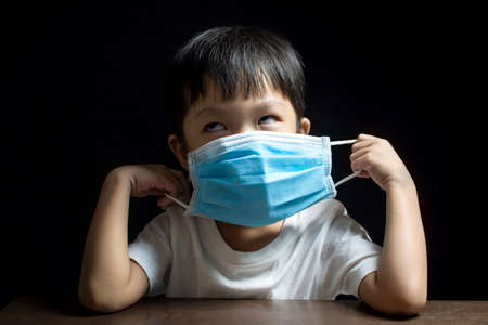 The little boy showed signs of refusing to wear the medical face mask , Coronavirus (COVID-19) prevention concept Reklamní fotografie