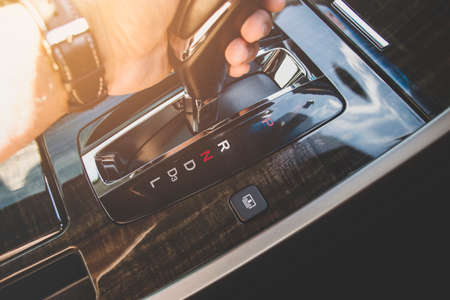 The driver's hand moved the gear selector to the reverse (R) mode of the automatic transmission in the car