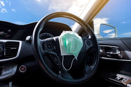 Surgical face mask placed on steering wheel in a car , Coronavirus (COVID-19) prevention concept