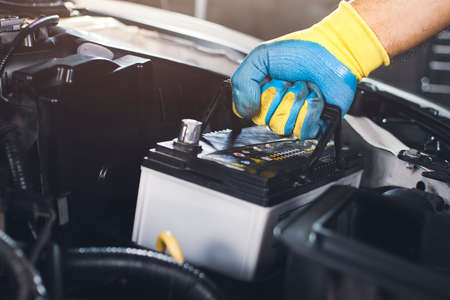 Technician is pulling up an car old battery for replacement Banque d'images