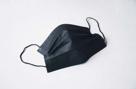 Black surgical face mask with ear strap on white background