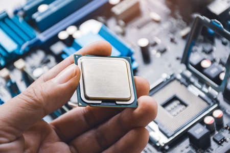 CPU processor chip in technician hand and computer motherboard background