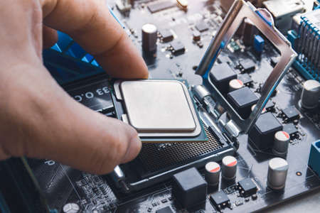 Technician install CPU processor chip in socket on computer motherboard