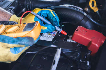 Technician checking DC voltage stable of the car battery with digital multimeter probe