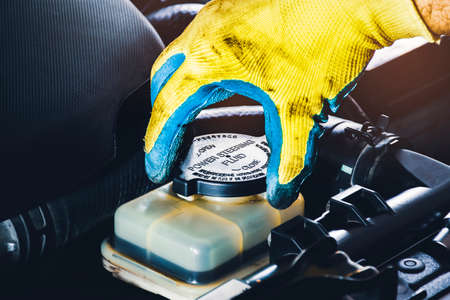 The mechanic hand is open or close the cap of the power steering fluid to check the hydraulic fluid level