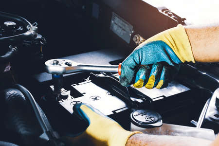 The Mechanic hand is fasten the bolt of battery Anode with socket wrench