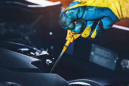 Technician hand pulling oil dipstick for checking lubricating oil level of the car engine 版權商用圖片