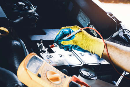 Technician to checking voltage stable of the car battery with digital multimeter probe 版權商用圖片