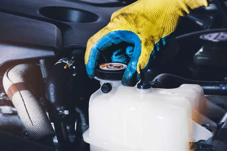 The mechanic hand is open or close the cap of coolant reservoir tank of car radiator to check the fluid level