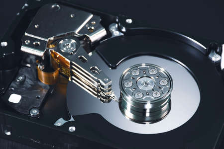 Close up internal of hard disk drive having a metal alloy disc platters and actuator arms inside with component