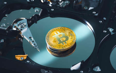 Close up golden bitcoin place on the platter of hard disk drive inside,cryptocurrency concept