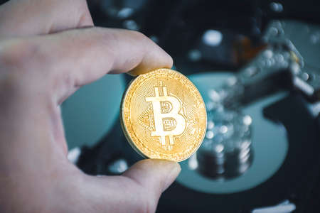 Close up of gold bitcoin in the hand with hard disk platters blurred on background 版權商用圖片