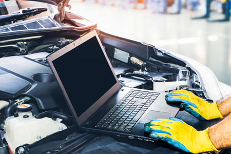 Technician tuning engine car with the computer laptop in repair garage,blank display