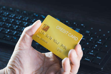 Credit card mockup in the hand with computer keyboard background