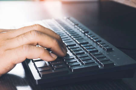 Human hand using computer keyboard on desk