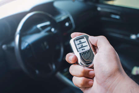 Car keyless entry remote in a hand of the owner car with car interior blurred background