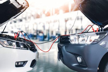 Sedan car jumper the battery cables to the pickup truck in repair garage 版權商用圖片