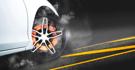 Disc brakes burn with high temperature and the smoke of racing cars on the racetrack at night 版權商用圖片