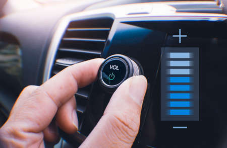 Car owner hand turning volume button of a car audio system in the car