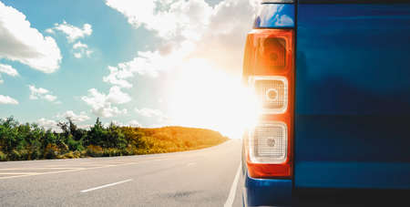 Highway with sunset and rear bumper of the blue car parked on the roadside 版權商用圖片