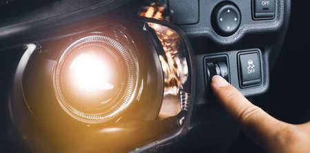 Driver hand adjusting headlight level switch and car headlight bright,Double exposure automotive concept 版權商用圖片