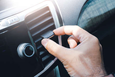 Driver hand adjusting wind direction of air vent on console in the car