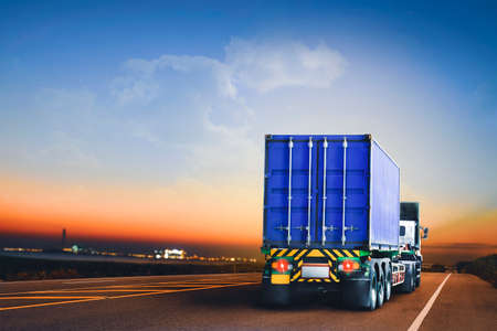 Trailer truck with container running on highway to the industrial estate at evening time