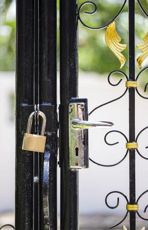 metal gate: closed padlock on the door of a metal gate Stock Photo