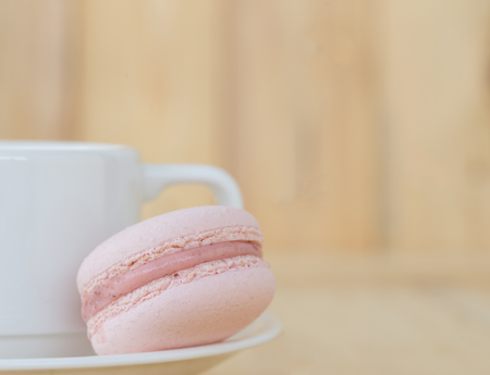 macaroon: Pink Macaroon with cup on wooden background. Stock Photo
