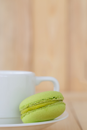 macaroon: Green Macaroon with cup on wooden background.