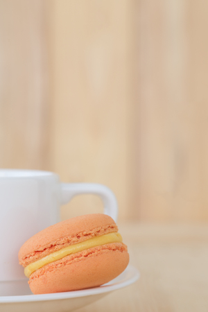 macaroon: Orange Macaroon with cup on wooden background.