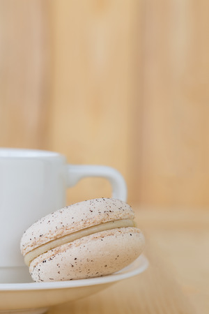 macaroon: Cream Macaroon with cup on wooden background.