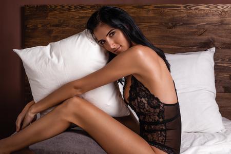 pretty dark hair young woman hug pillow on the bed