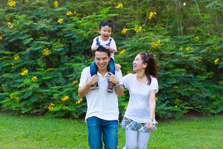 Asian couple running with their young son in the park photo