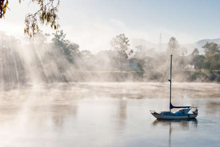 wheather: Foggy morning on a river with boat