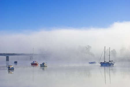 Boats on a foggy river photo