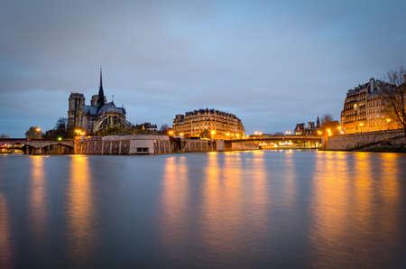 notre dame cathedral: Notre Dame Cathedral and river Seine at twilight (Paris) Stock Photo