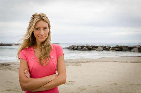 Schöne blonde Mädchen vor dem Strand stand mit verschränkten Armen