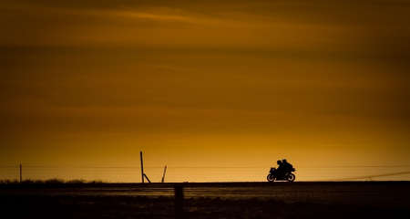 Motor bike in on a road in the sunset photo