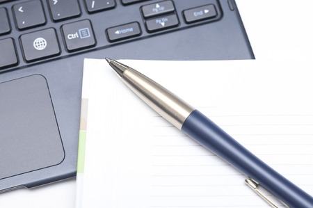 Notepad and pen on keyboard on white background