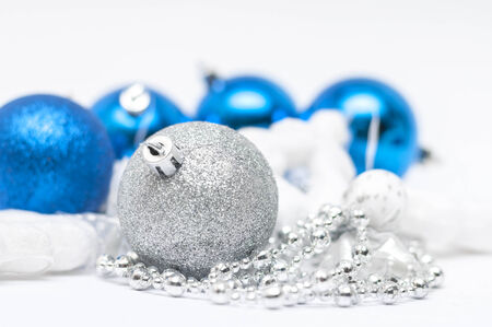 Christmas silver ball in  focus and blue balls in background with ribbons and snow photo