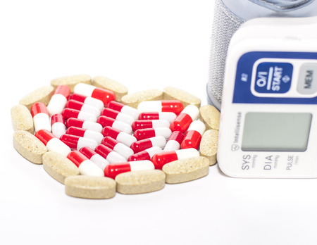 blood pressure device and tablets in heart-shaped arrangement, symbol photo of heart disease, diagnosis and medication