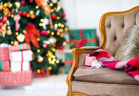 Kerstboom en kerst cadeau dozen in het interieur met een open haard. Kerst woonkamer met open haard en een fauteuil