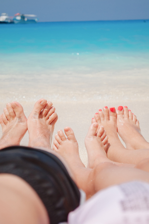 Family of three people lying on the beach