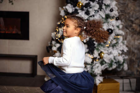 Little girl dancing next to the Christmas trees